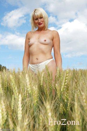 Красивая зрелая блондинка позирует на природе