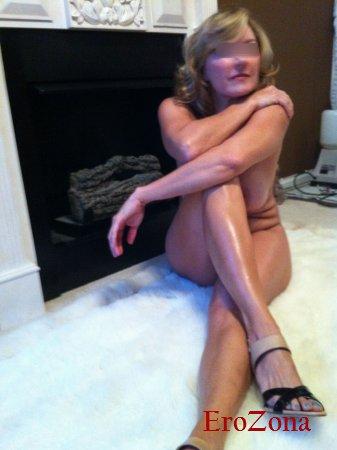 Роскошная дама эротично позирует обнаженной у камина показывая свои стройные ножки